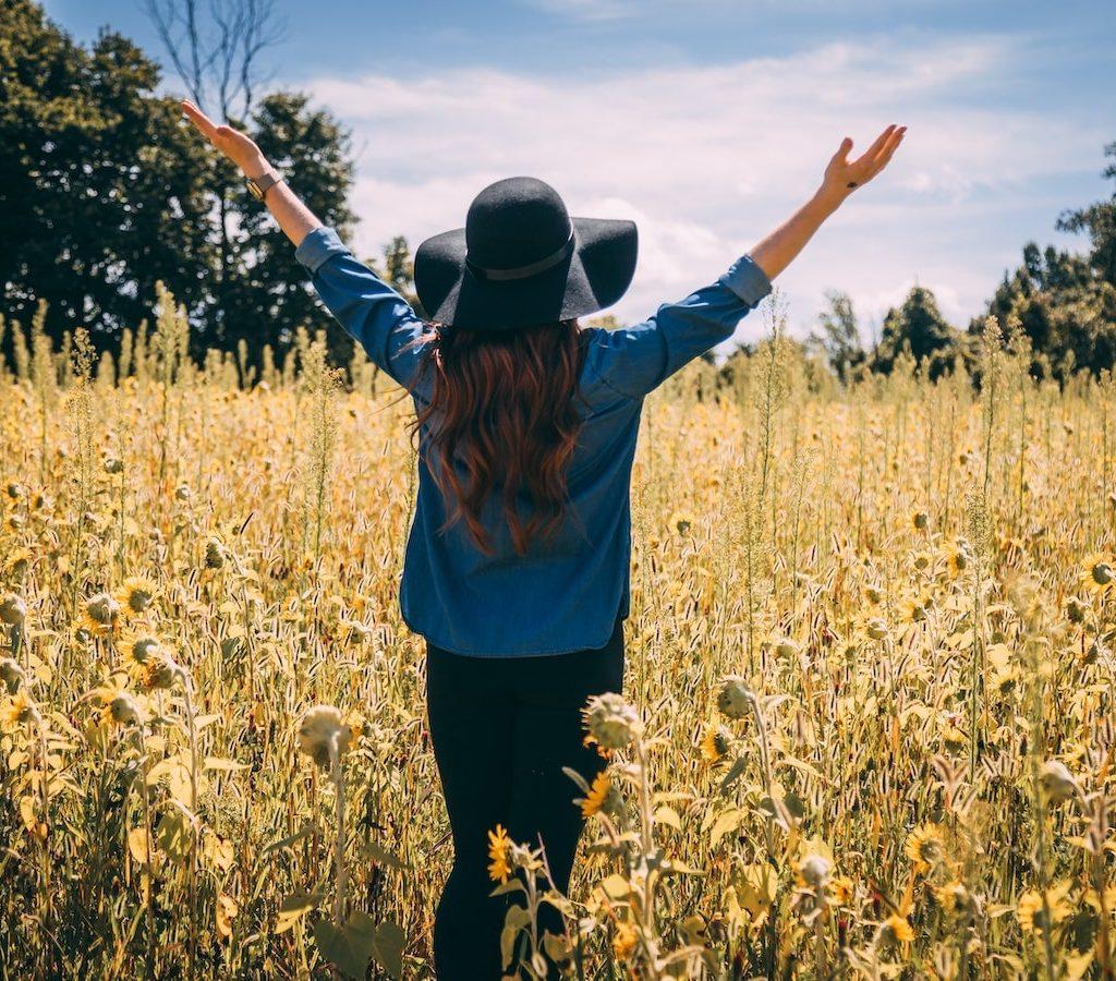 junge Frau mit Hut läuft dankbar und mit gehobenen Armen über ein Blumenfeld und verspürt Dankbarkeit