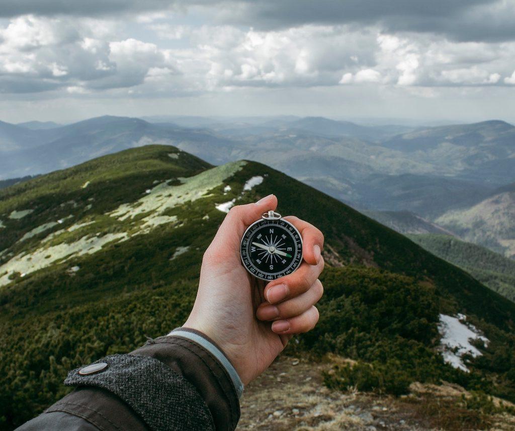 eine Hand hält einen Kompass vor einer Berglandschaft, Orientierung Ziele setzen Vision