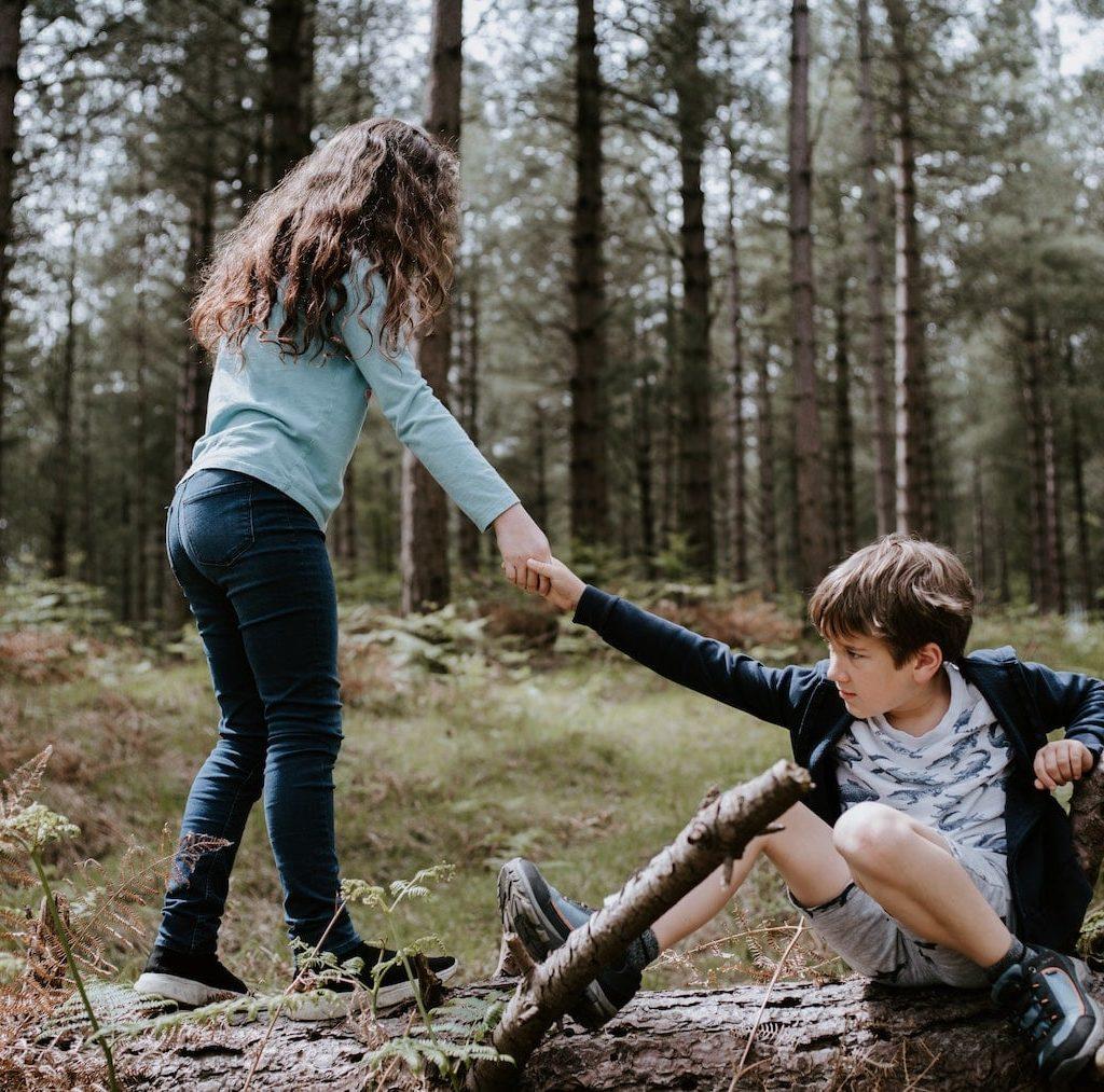 kleines Mädchen hilft einem kleinen Jungen vom Boden aufzustehen