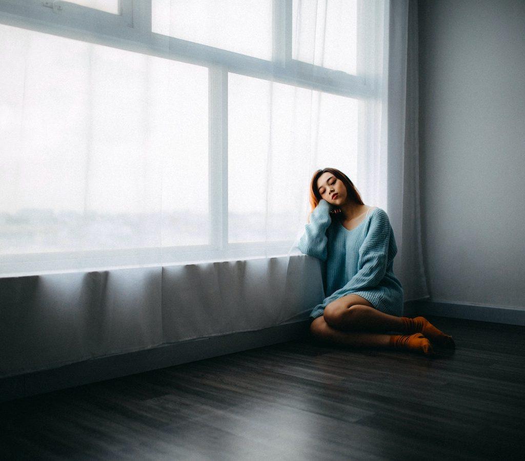 junge Frau sitzt alleine und traurig auf dem Boden und verspürt innere Leere