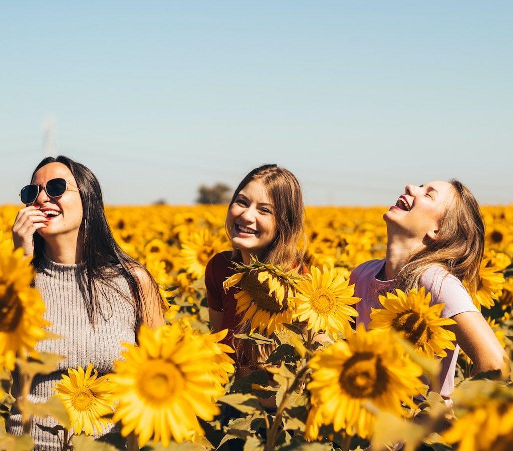 drei junge Frauen lachen gemeinsam in einem gelben Sonnenblumenfeld - mit Freunden Einsamkeit überwinden