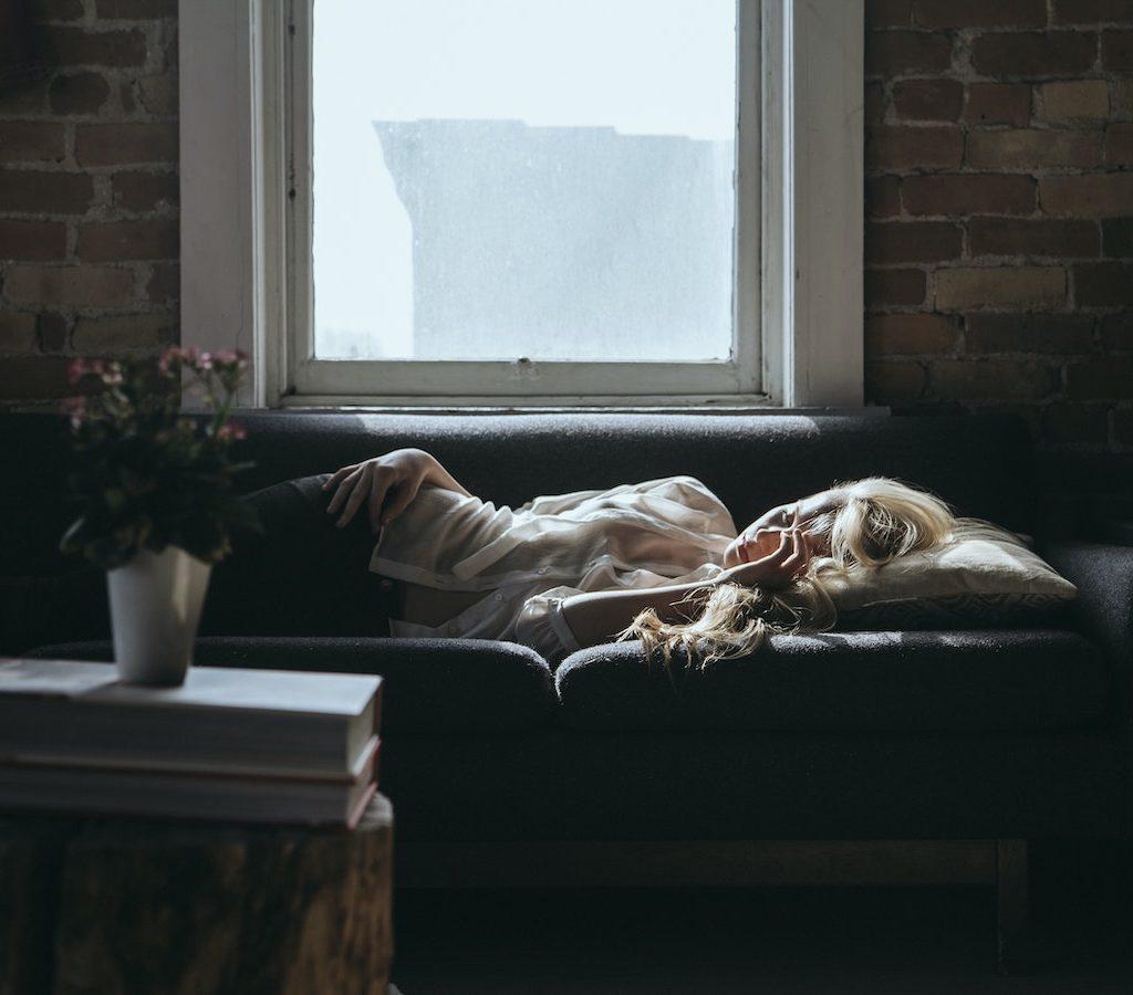 junge blonde Frau ist faul, müde und träge. Sie legt auf der Couch und hat Schwierigkeiten ihre Faulheit zu überwinden