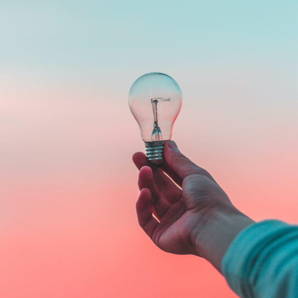 eine Hand hält eine Glühbirne in den Sonnenaufgang - Inspiration