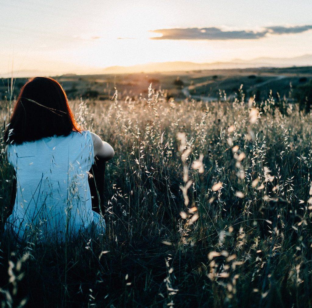 junge Frau sitzt einsam im Feld und schaut in die Ferne - Einsamkeit