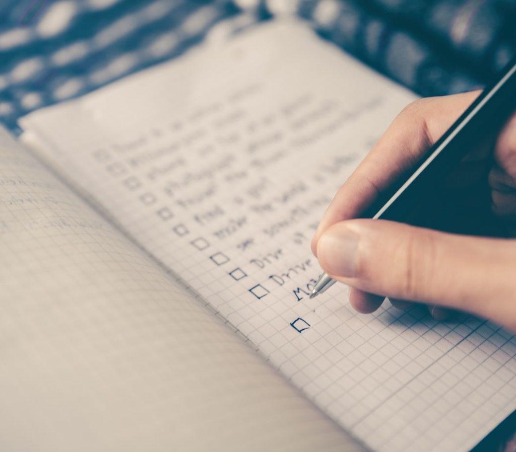 eine Hand schreibt einen Plan, eine Strategie in einen Notizblock auf