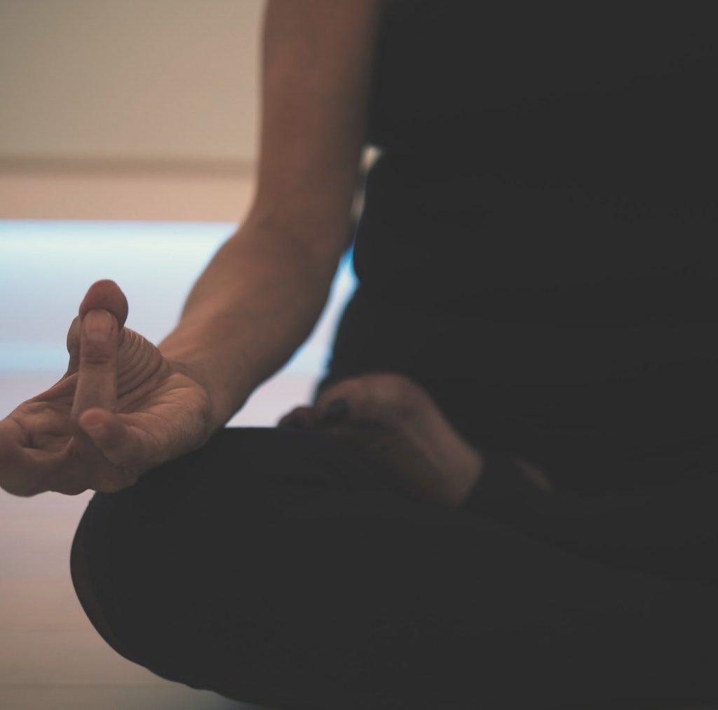 junge Frau sitzt auf dem Bett und meditiert - Meditation hilft die Innere Leere zu füllen