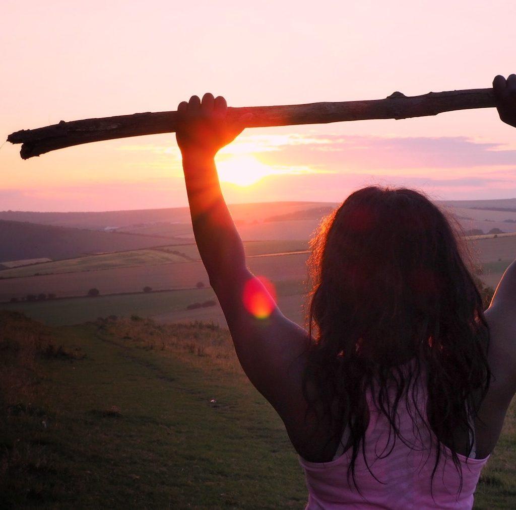 junge Frau hat eine Herausforderung bewältigt und hält ihre Hände, die einen Ast halten hoch