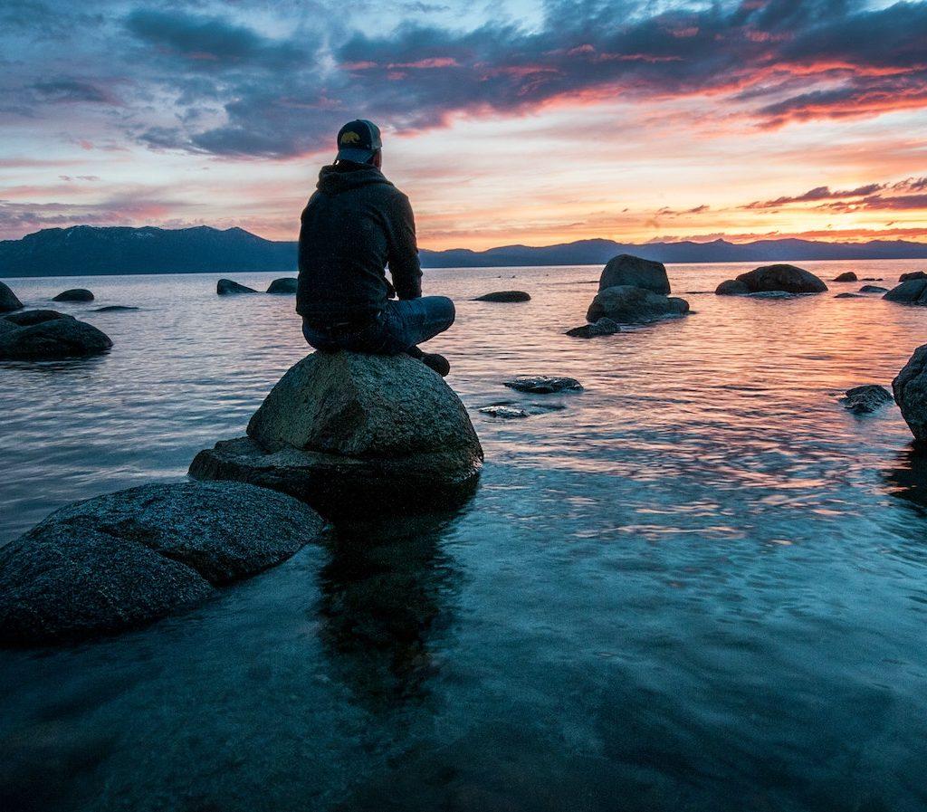 junger Mann sitzt alleine auf einem Stein an einem See und schaut in den Sonnenuntergang - Einsamkeit