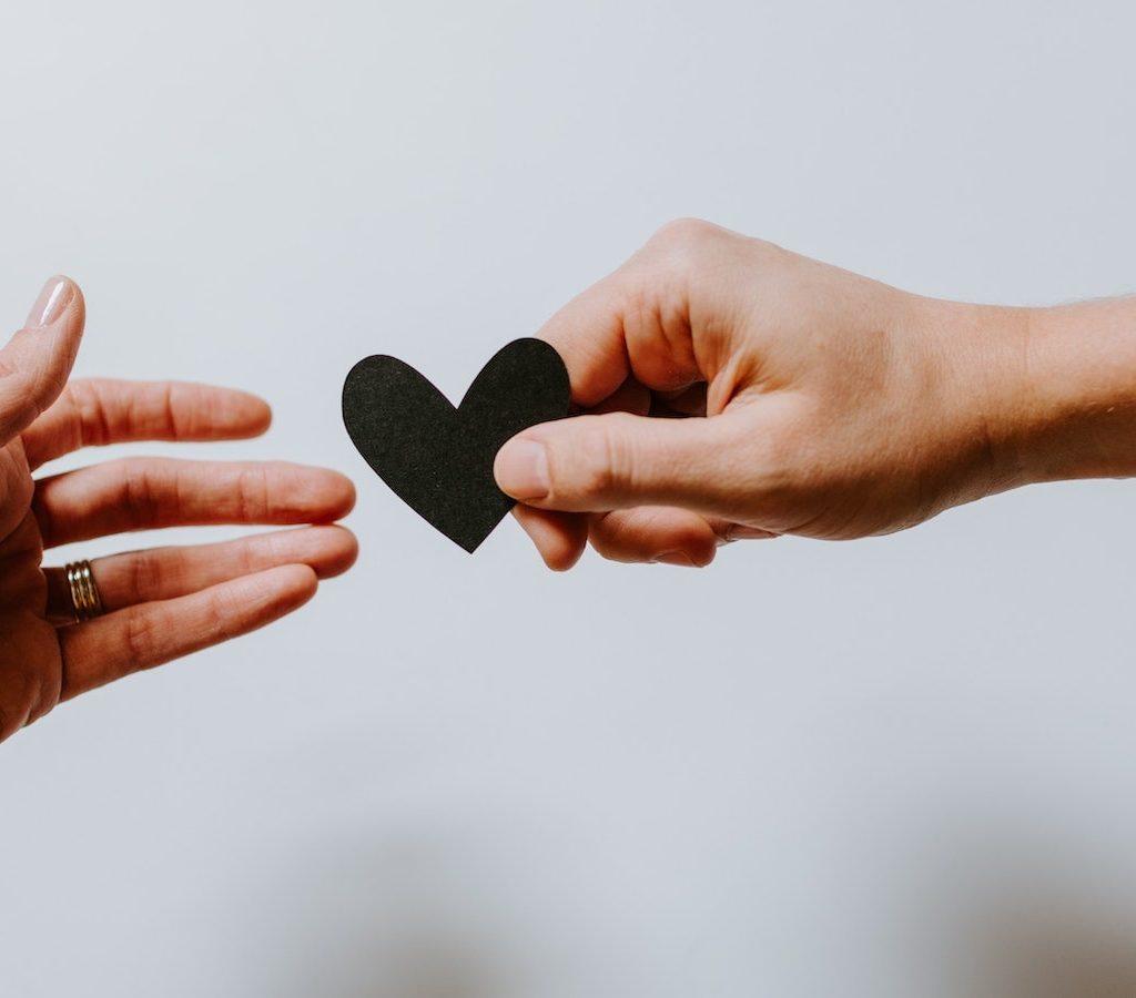 eine Hand reicht einer anderen Hand ein kleines schwarzes Herz auf Pappe als Zeichen der Dankbarkeit