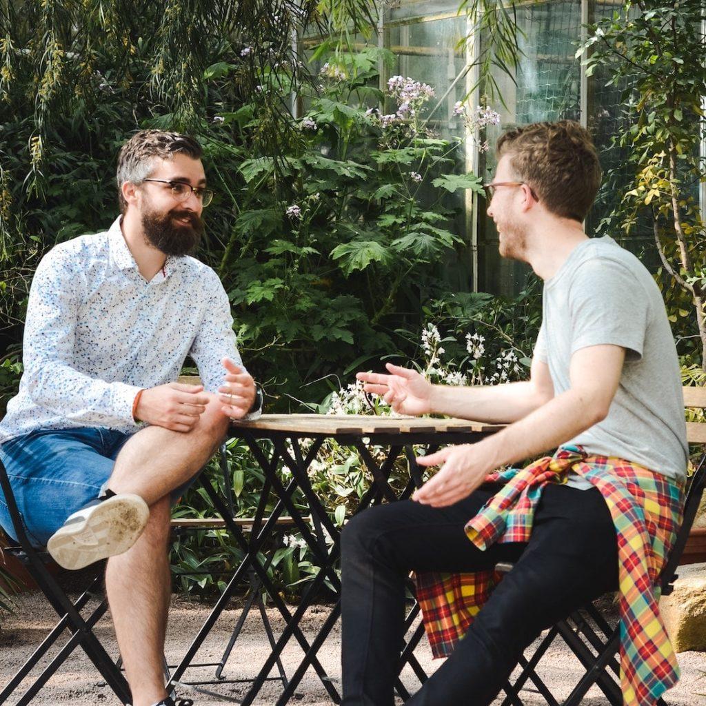 zwei junge Männer sitzten in einem Café an einem Tisch und unterhalten sich