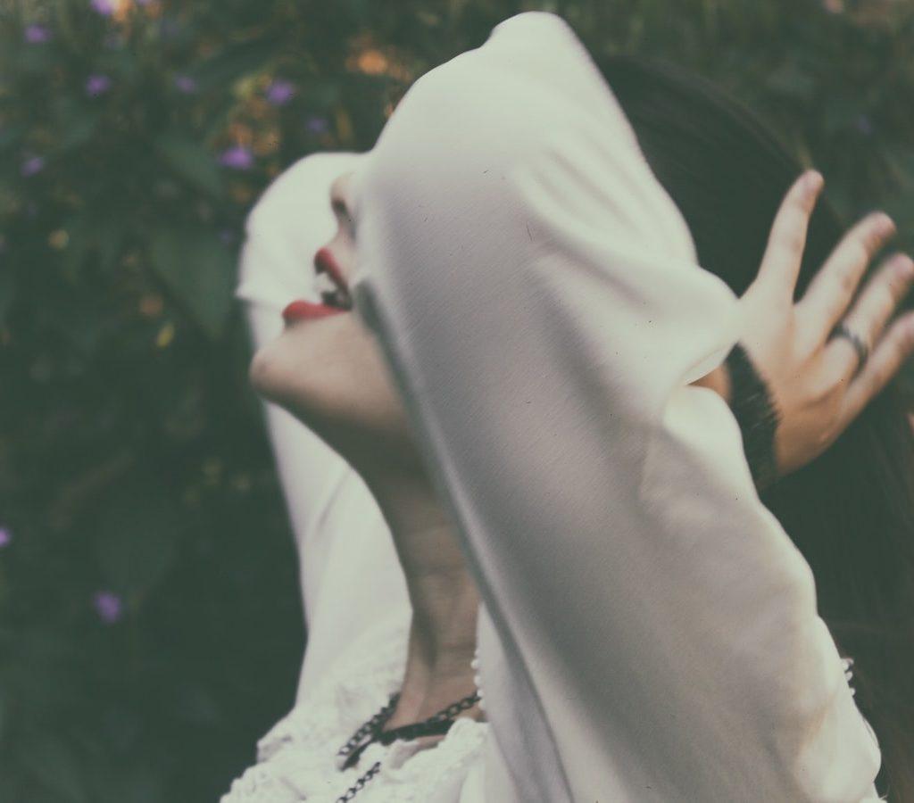 junge Frau ist dankbar und hält ihre Hände an ihren Kopf