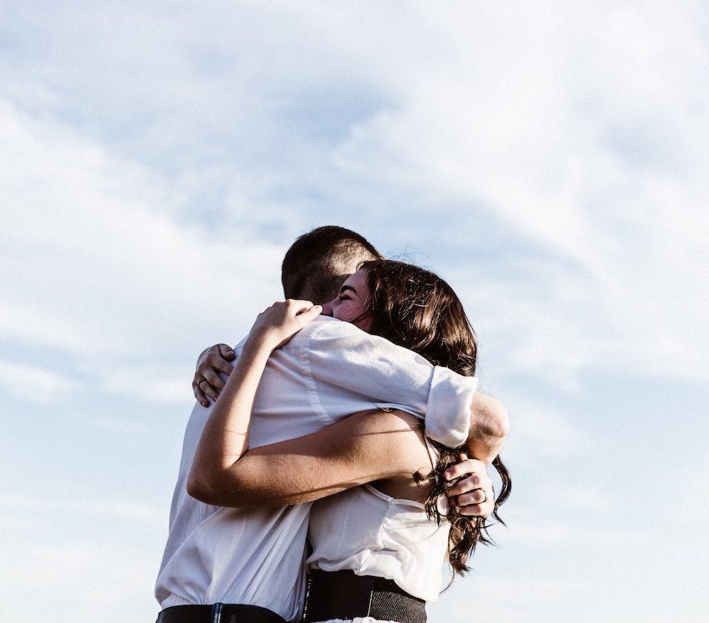 eine junge Frau und ein junger Mann umarmen sich ganz fest und sind beide froh und zeigen Dankbarkeit