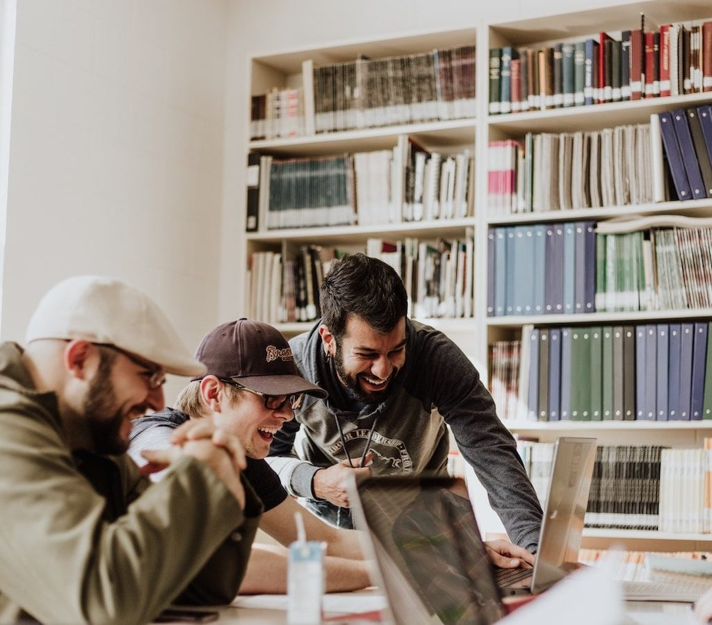 junge Männer in der Bibliothek arbeiten gemeinsam an ihren Computern und lachen - Einsamkeit überwinden