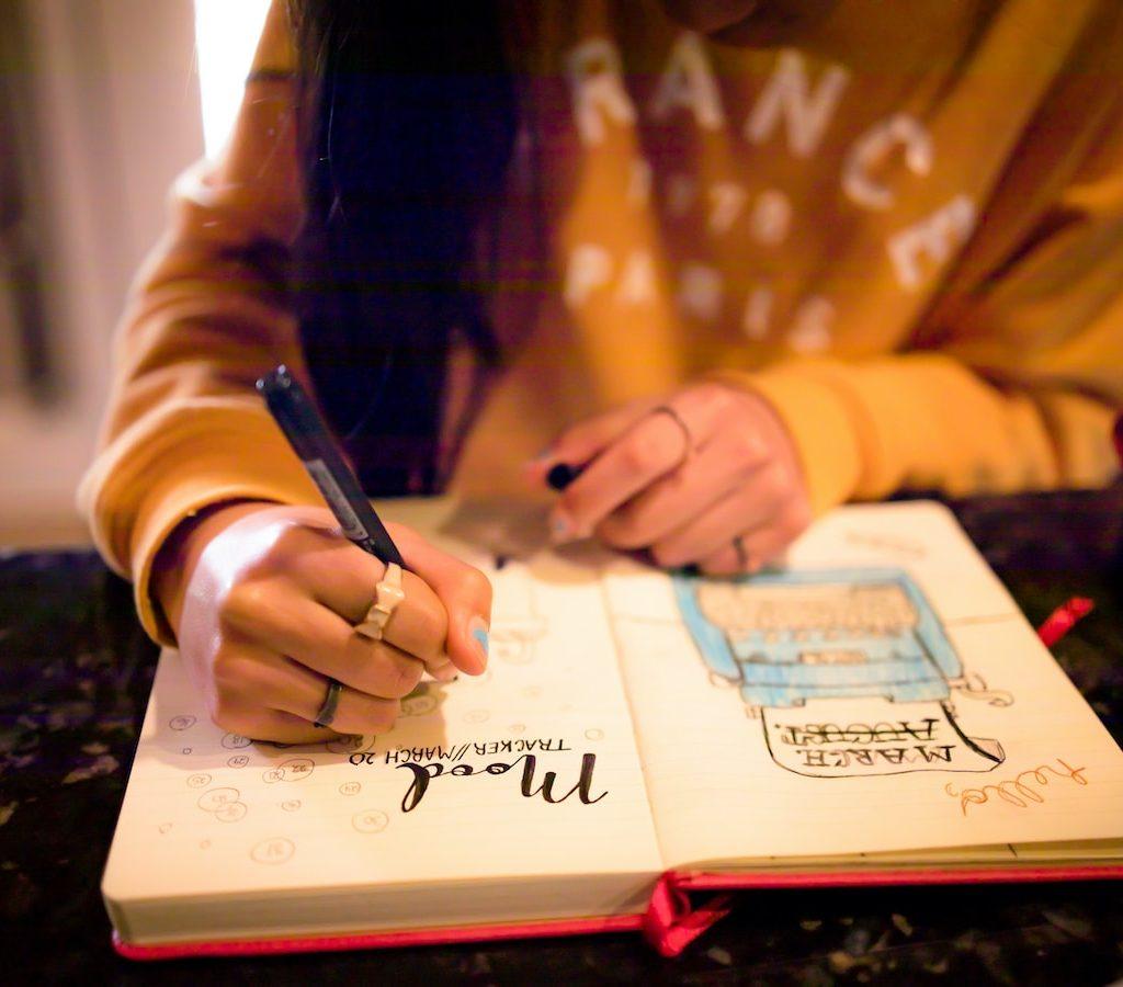 junge Frau schreibt in ihr Dankbarkeitstagebuch