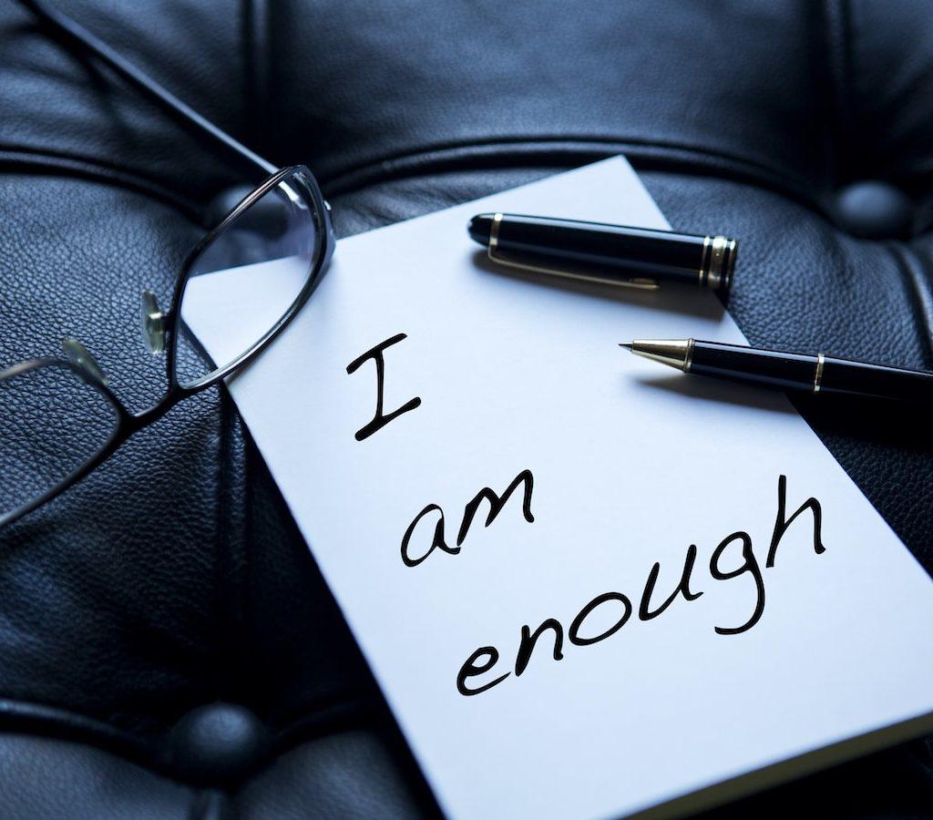 """ein Zettel mit der Aufschrift """"i am enough"""", zu Deutsch """"ich bin genug"""" liegt neben einer Lesebrille auf einer schwarzen Ledercouch"""