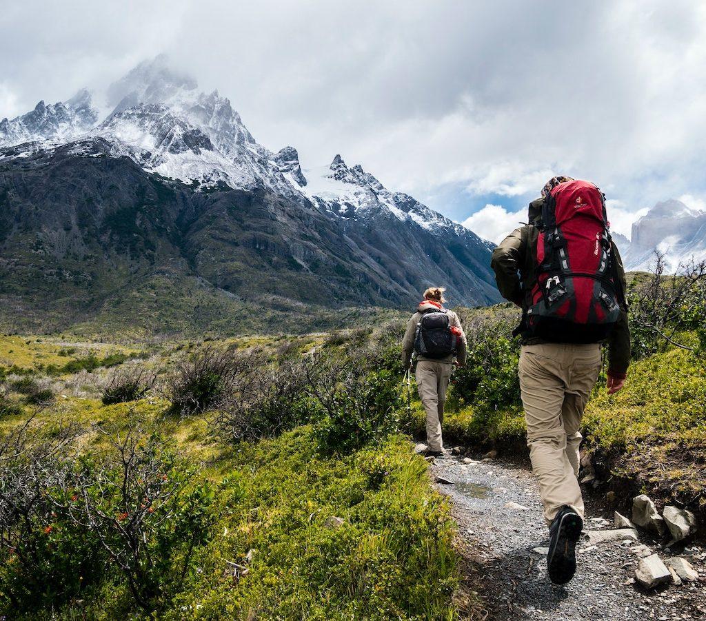 zwei junge Leute mit Rucksäcken wandern in den Bergen - Bewegung gegen Faulheit