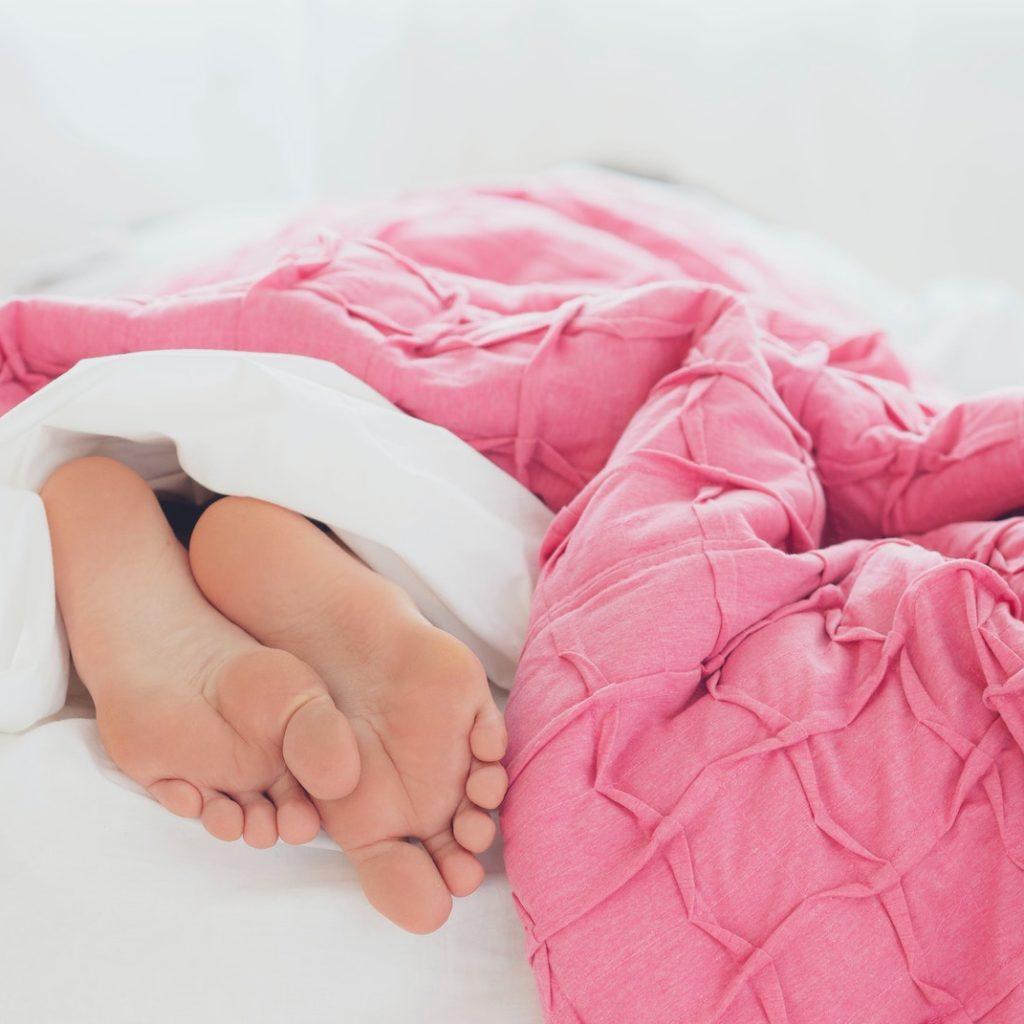 Füße schauen unter einer rosa Decke hervor - Dankbarkeit kann einen guten Schlaf fördern