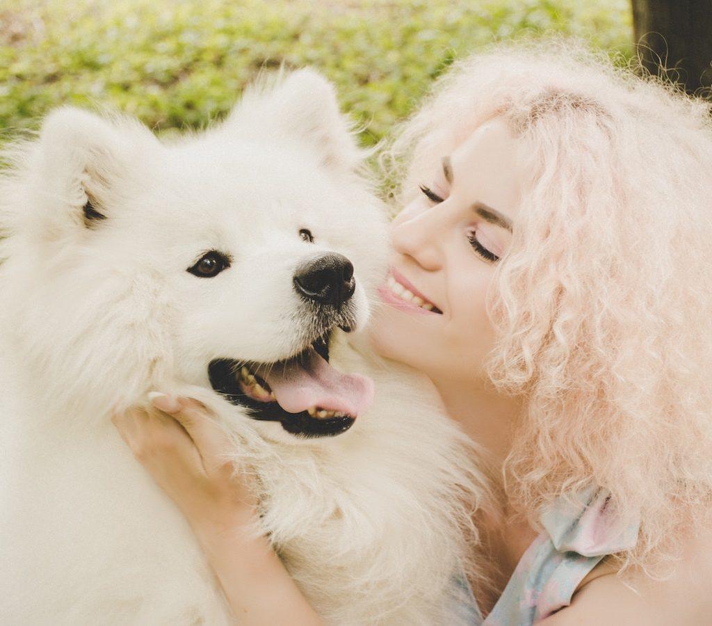 junge blonde Frau spielt mit einem weißen Hund ist fröhlich