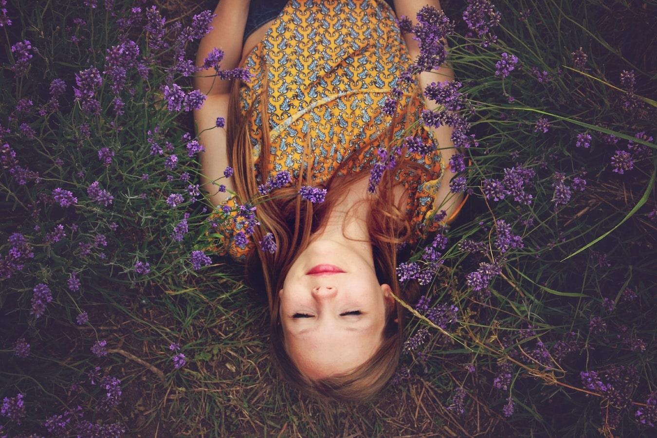 junge Frau liegt entspannt in einem Lavendelfeld