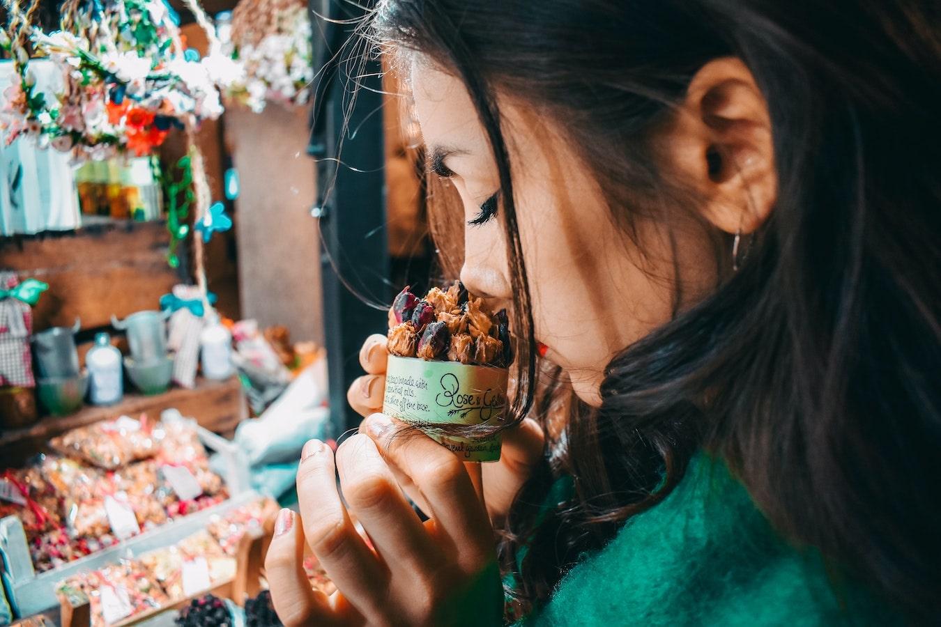 junge Frau riecht an getrockneten Rosen und spürt die Wirkung von Aromen